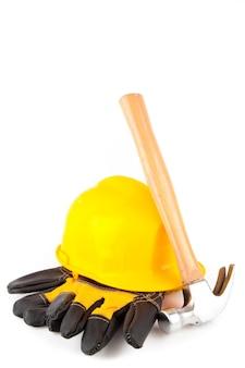 Hammer lehnt gegen schutzhelm und handschuhe des erbauers