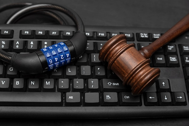 Hammer mit kombinationsschloss auf computertastatur. datenschutzkonzept.