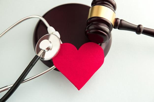 Hammer mit rotem herzen, pillen, stethoskop und büchern auf dem tisch. medizinrechtliches konzept.
