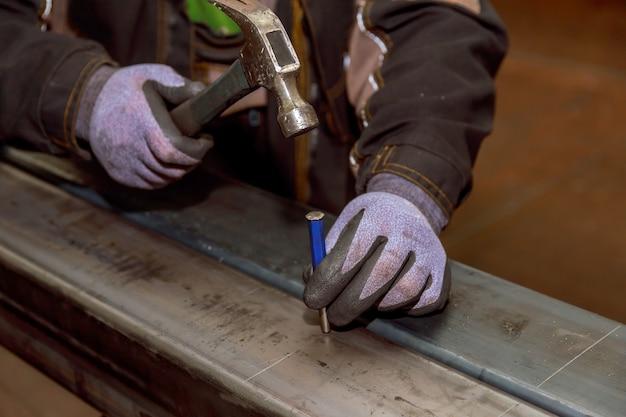 Hammer, nagelschlag. markierung auf einer metalloberfläche zum bohren von löchern mit einem quadrat und einem bremssattel.