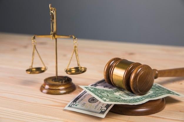 Hammer richter, waage und geld auf dem tisch