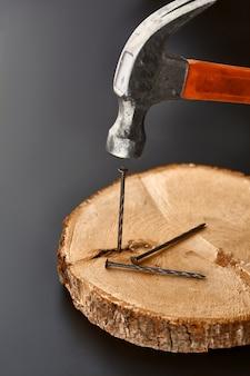 Hammer treibt einen nagel in einen baumstumpf. professionelles instrument, bauausrüstung, befestigungselemente, befestigungs- und schraubwerkzeuge
