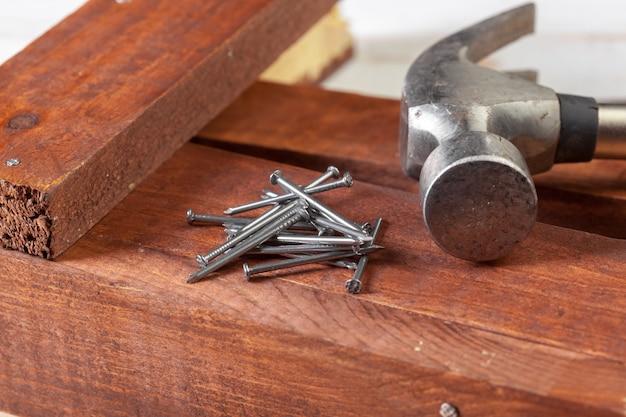 Hammer und nägel auf hölzernem hintergrund
