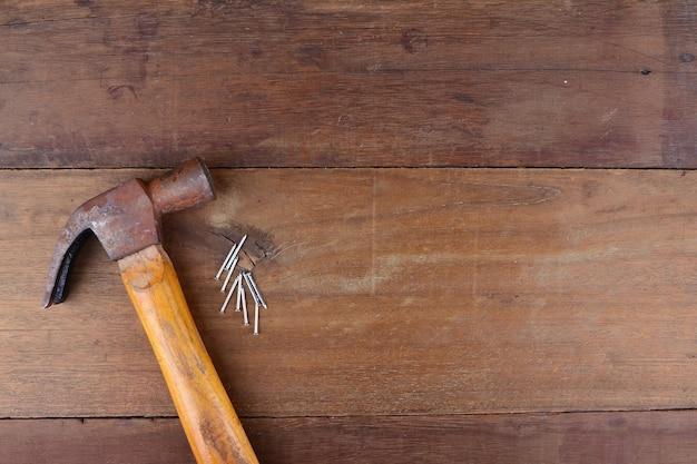 Hammer und nägel auf holzhintergrund