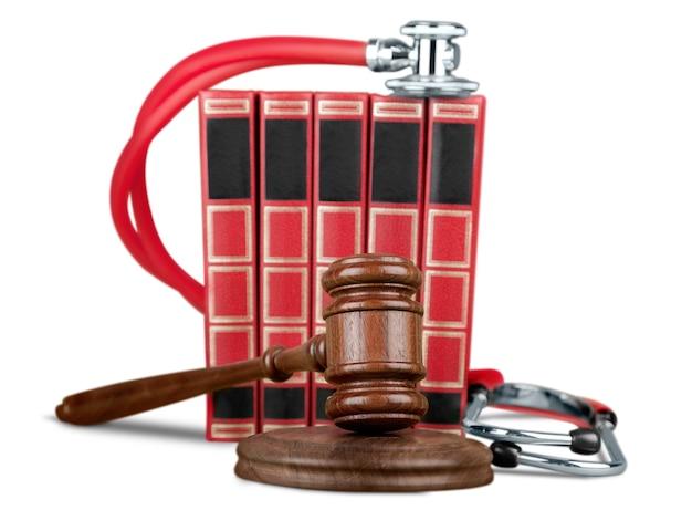 Hammer und stethoskop im hintergrund, symbolfoto für pfusch und medizinische fehler