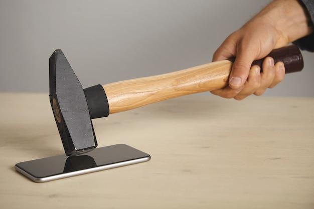 Hammer wird auf dem smartphone-bildschirm heruntergebracht, glas noch intakt