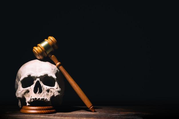 Hammerhammer des hölzernen richters auf menschlichem schädel gegen schwarzen hintergrund