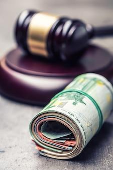 Hammerhammer des richters. gerechtigkeit und euro-geld. euro währung. gerichtshammer und gerollte euro-banknoten. darstellung von korruption und bestechung in der justiz.
