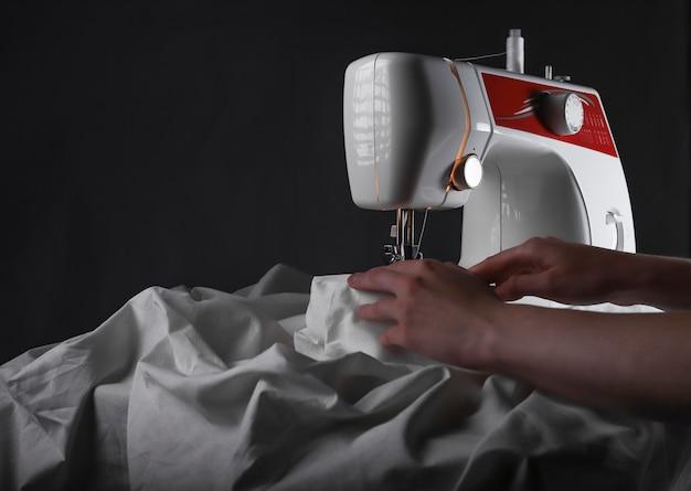 Hand an der nähmaschine während des arbeitsprozesses mit textil
