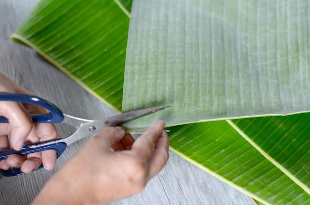 Hand auf bananenblatt schneiden