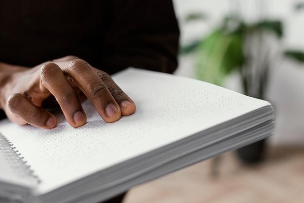 Hand auf braille-notizbuch nahaufnahme
