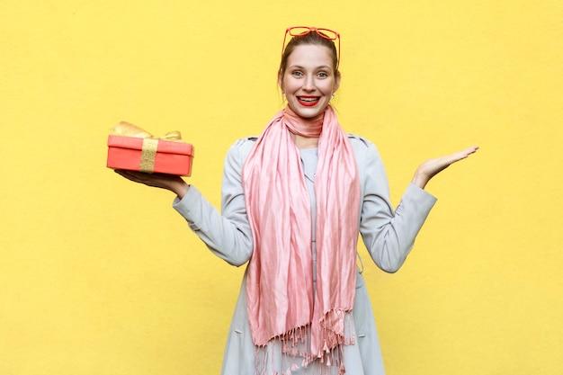 Hand auf den seiten und hält die weihnachtsboxfrau, die kamera anschaut und zähneknirschend lächelt