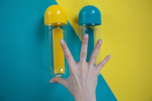 Hand auf einem hintergrund von gelben und blauen flaschen auf einem blauen und gelben hintergrund