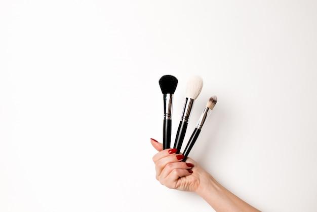 Hand auf einem weißen hintergrund hält make-upbürsten
