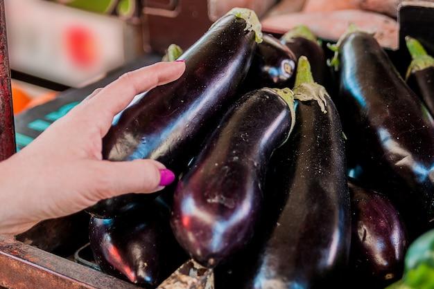 Hand auf frische auberginen - auberginen, nahaufnahme. weibliche wahl. freudige junge weibliche kunde wahl frische aubergine auf fruchtmarkt