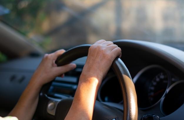 Hand auf halten autolenkrad. frau fahren sie vorsichtig mit dem auto.