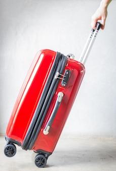 Hand auf rotem reisendem koffer