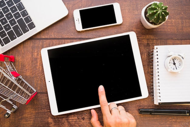 Hand auf tablette nahe smartphone, laptop und einkaufslaufkatze