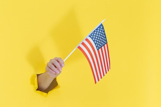 Hand aus einem loch in gelbem papier hält eine amerikanische flagge mit blauen sternen. amerika-unabhängigkeitstag-konzept. hand, die amerikanische flagge hält