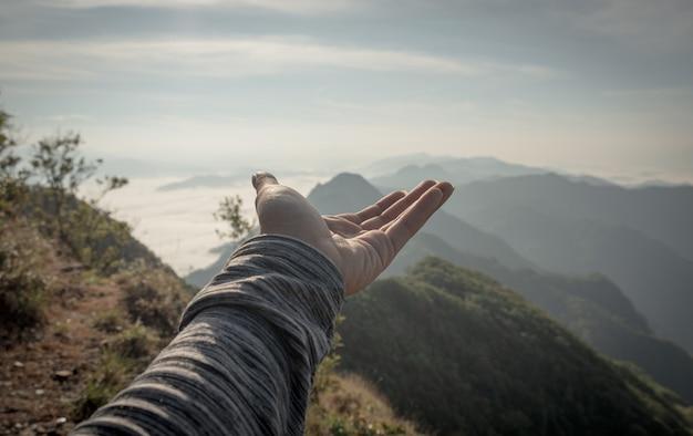 Hand ausgestreckt, um tageslicht und bergblick zu erhalten
