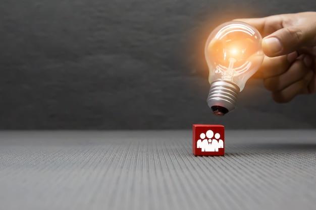 Hand ausgewählte glühbirne auf hölzernem spielzeugblock.