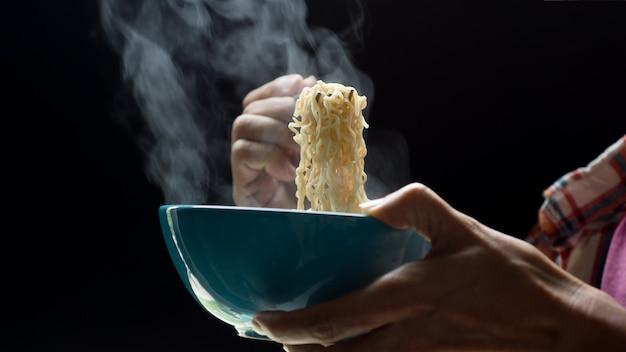 Hand benutzt essstäbchen zu geschmackvollen nudeln mit dampf und rauche in der schüssel auf hölzernem hintergrund