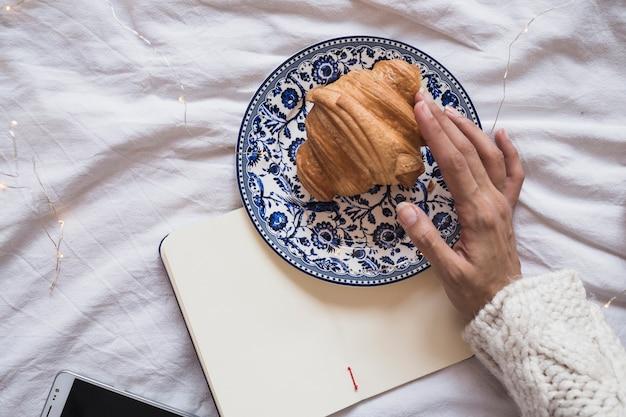 Hand berühren croissant auf platte