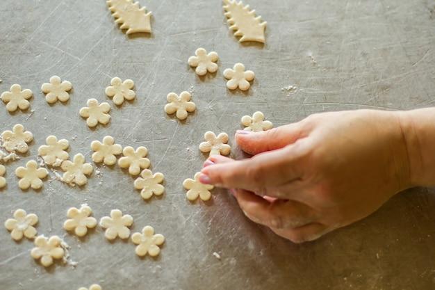 Hand berührt blume aus teig. kleine stücke von rohem gebäck. baker macht dekoration für lebensmittel. rezept und kunstwerk.