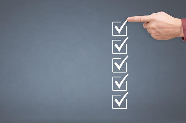 Hand-checkboxen mit markierungsstift auf checkliste oder to-do-liste mit kopierbereich. grauer hintergrund. hände aktivieren alle kontrollkästchen. listenmodell zu tun. checklistenmodell und mannhand