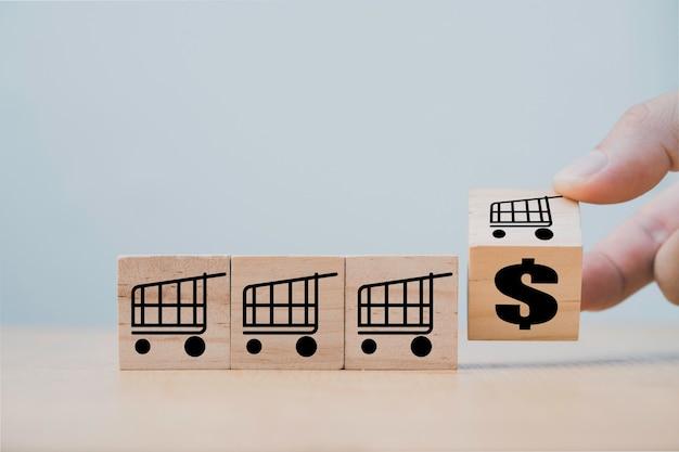 Hand, das hölzernen würfelblock für wechselwagen-einkaufswagen zu dollarzeichen, marketing- und verkaufswachstumskonzept umdreht.