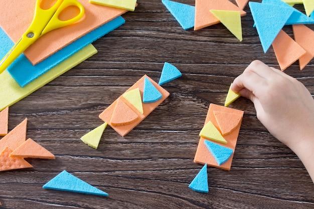 Hand das kind sammelte eine süße figur in tangram puzzle quadratischen holztisch oben.
