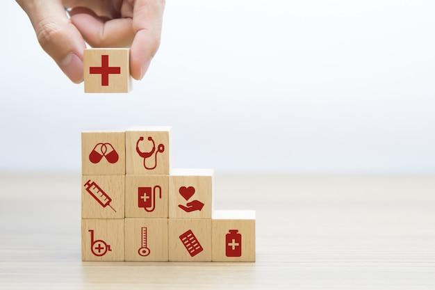 Hand, das medizinisches und gesundheitssymbol auf einem hölzernen spielzeugblock aufnimmt.