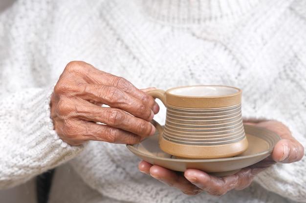 Hand der älteren frauen, die eine tasse grünen tee halten