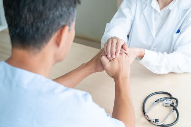 Hand der ärztin, die ihren älteren patienten festhält