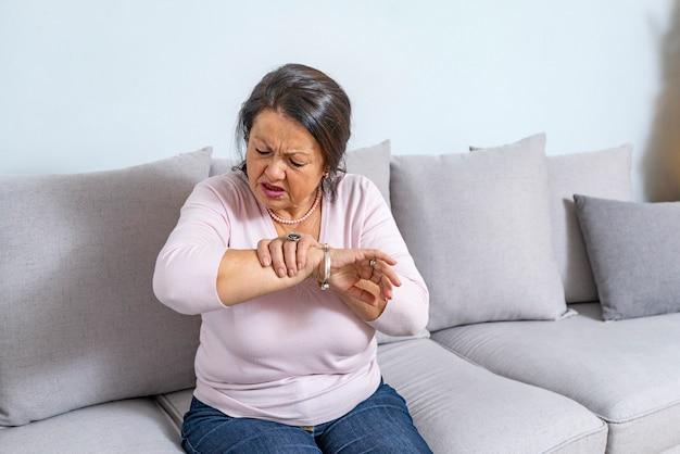 Hand der alten frau, die ihren ellbogen leidet unter ellbogenschmerz hält.