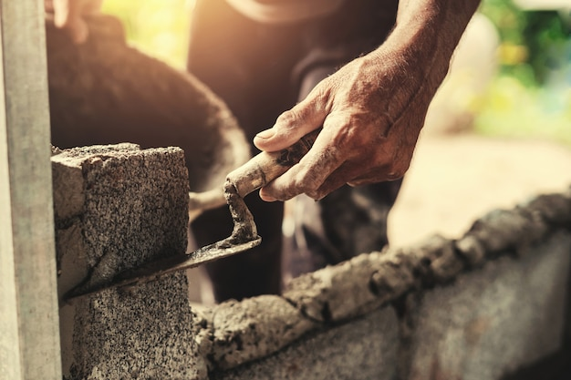 Hand der arbeitskraft zement auf backsteinmauer an der baustelle vergipsend
