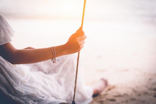 Hand der asiatin auf dem weißen kleid, das auf schwingen am strand sitzt