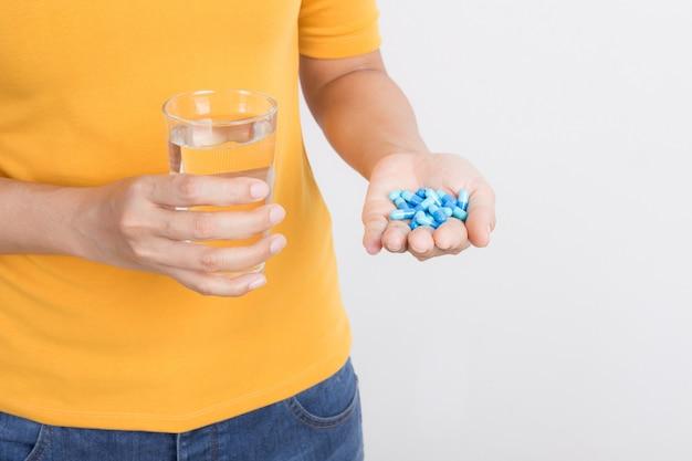 Hand der asiatin, die kapsel und glas auf weißem hintergrund hält