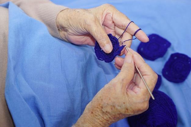 Hand der asiatischen älteren frau häkeln dunkelblaues garn
