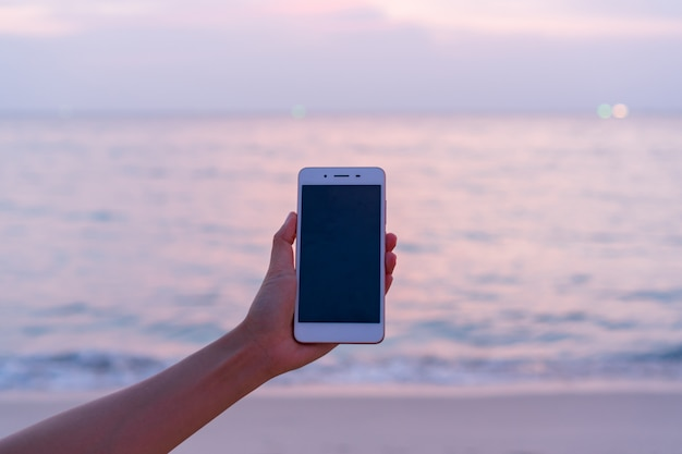 Hand der asiatischen frau des jungen reisenden, die smartphone zu vdo-anruf zu ihrer familie im urlaub verwendet. sommer am strand konzept. nahaufnahme, speicherplatz kopieren