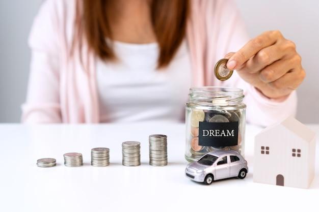 Hand der asiatischen frau, die münze in glasglas mit modellhaus und auto setzt. einsparungen, geld sammeln konzept