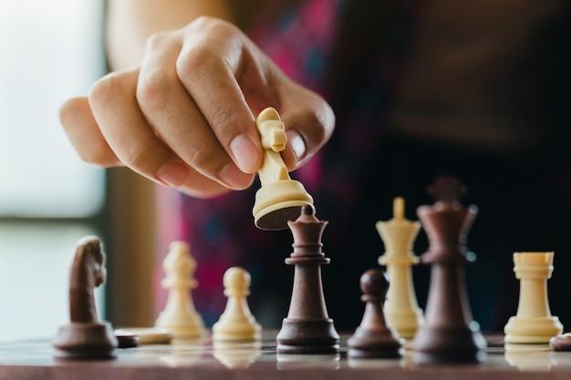 Hand der beweglichen schachfigur des mannes in konkurrenz