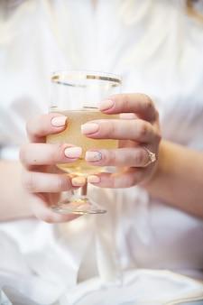 Hand der braut mit dem hochzeitsring, der ein glas champagner und luftblasen anhält