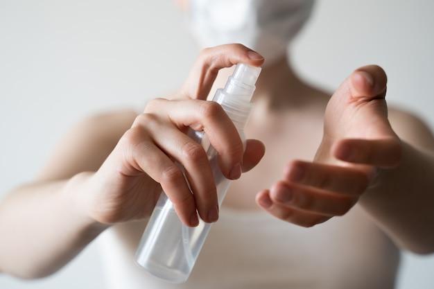 Hand der dame, die alkoholspray oder antibakterielles spray aufträgt, um die ausbreitung von keimen, bakterien und viren zu verhindern.