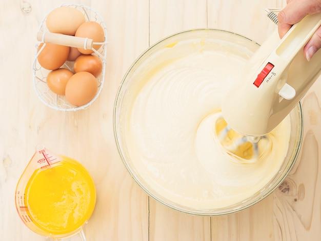 Hand der dame, die kuchen unter verwendung der handmischmaschine mit ei und butter vorbereitet