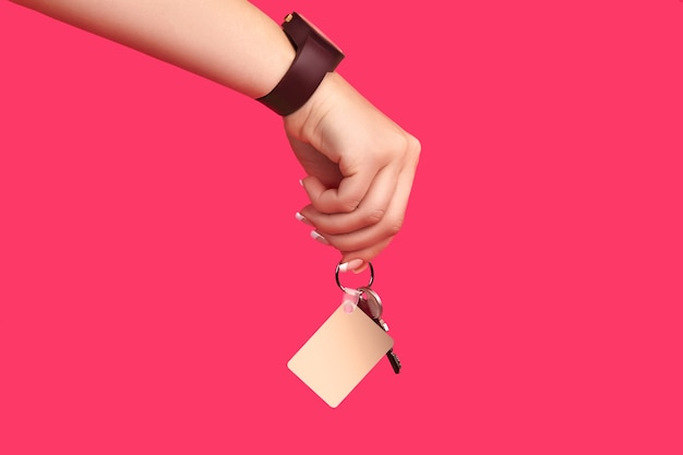 Hand der dame in der braunen uhr hält einen schlüssel mit leerem weißen quadratischen plastikschlüsselbund