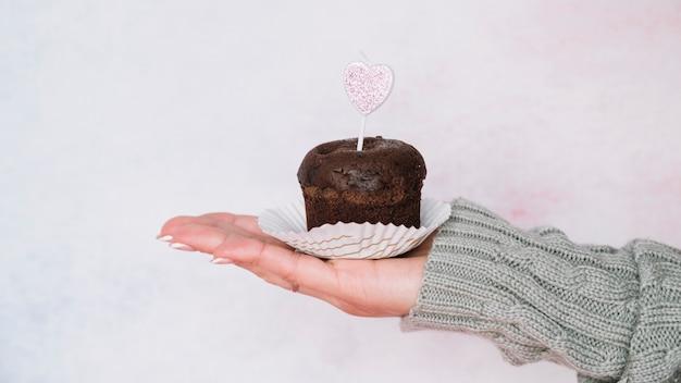 Hand der dame in der strickjacke mit schokoladenmuffin mit kerze