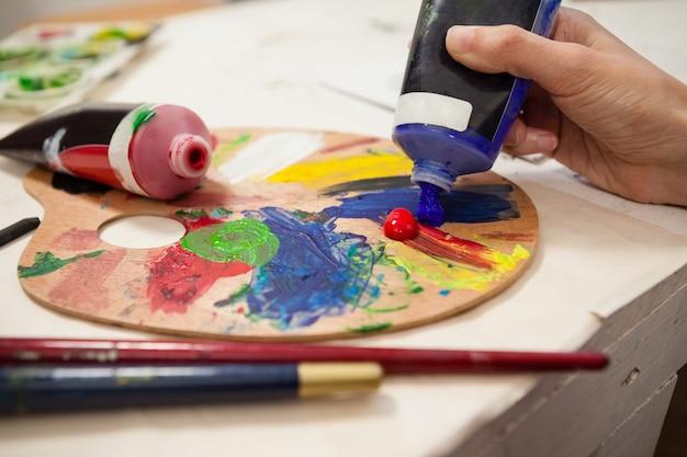 Hand der frau blaue farbe in palette einsetzend