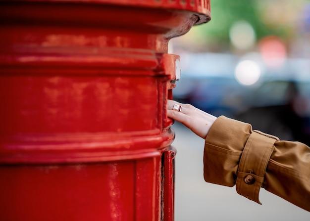 Hand der frau, die brief in einem roten kasten sendet
