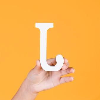 Hand der frau, die das weiße alphabet j anhält